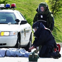 The Erie police's bomb squad examines the dead body of Brian Wells after a collar bomb locked to his neck exploded. JANET B. KUMMERER/ERIE TIMES-NEWS