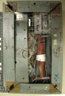 The FBI lab in Quantico, Va., used evidence collected from the scene of the bomb blast to reconstruct the bomb mechanism that hung from the neck of Brian Wells. Only one of the pipe bombs exploded. A metal plate covers the kitchen timers that were so crucial to the bomb's design; the metal mesh was a booby trap designed to detonate the bomb if the mesh touched the metal of the frame. The entire contraption weighed 10 to 15 pounds. FBI photo, used as evidence at trial