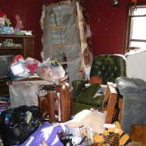 "Piles of junk and rotting food greeted Erie police officers and FBI agents when they searched Marjorie Diehl-Armstrong's house after September 21, 2003. They were looking for evidence that she fatally shot her boyfriend Jim Roden and helped place his body in a freezer in Bill Rothstein's garage. Diehl-Armstrong had history of hoarding government-surplus food. ""I've dealt with corpses with the flesh falling off. This is worse,"" a veteran Erie police officer said of Diehl-Armstrong's house. FBI photo, used as evidence at trial"