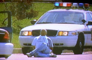 """Pizza deliveryman Brian Wells moments before the collar bomb locked to his neck exploded, killing him instantly. He had just robbed a bank in Summit Township, outside Erie, Pennsylvania, on August 28, 2003. The bomb is underneath his white T-shirt, which is a knockoff for Guess jeans. Wells' hands are cuffed behind his back. """"I don't have a lot of time,"""" Wells told the Pennsylvania State Police. WJET-TV, the ABC affiliate in Erie, filmed the entire episode. ERIE TIMES-NEWS, COURTESY OF WJET-TV"""