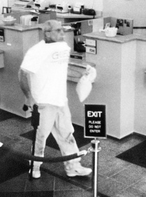 Brian Wells heads out of the PNC Bank in the Summit Towne Centre after robbing it of $8,702. Wells is carrying the cash in a white canvas bag; in his left hand is a homemade cane-shaped shotgun. He is sucking on a lollipop he grabbed while in the bank. The collar bomb is protruding from under his white T-shirt. He had demanded $250,000 from the chief teller, but left with whatever money she could give him. ERIE TIMES-NEWS, via FBI